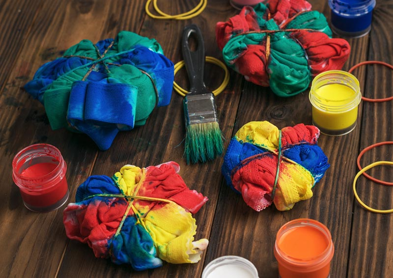 Shirts and clothing items wrapped in rubber bands and colors applied to create tie dye style items. Open paints and a paint brush on the table between clothing pieces.