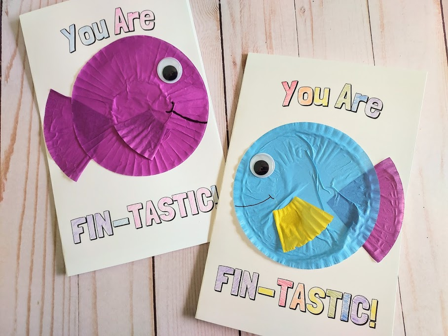 Two completed printable cards that say You Are Fin-Tastic. Words are colored in. Left card has a purple fish made from paper baking cups. Card on the right has a blue, purple, and yellow cupcake liner fish.