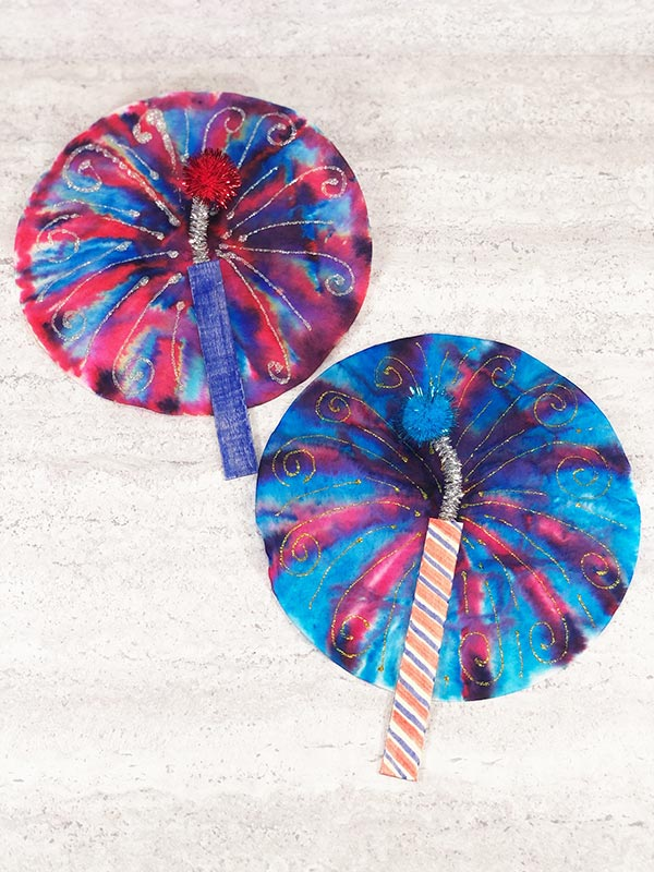 Two completed coffee filter fireworks crafts laying near each other at an angle. One has more red on the filter with a blue craft stick. The other has more blue on the filter and a striped craft stick.