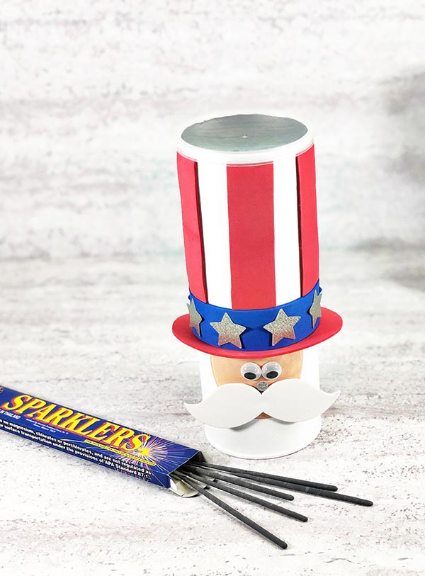 Completed Uncle Sam chip can craft project standing up next to a small box of sparklers with some of the sparklers spilling out.