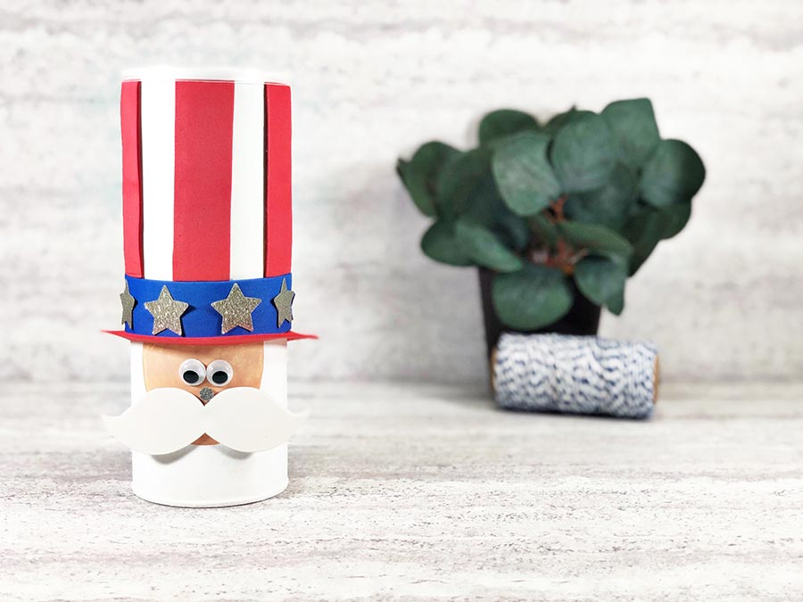 Finished Uncle Sam chip can Fourth of July craft for kids. Chip can made to look like Uncle Sam's hat and face in a cute style. Off to the right in the back is a small fake green plant and a roll of twine.
