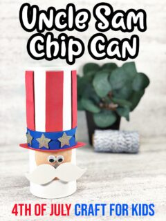 Chip can made to look like Uncle Sam's head wearing a hat. Small green plant out of focus in background. Top of picture has white text outlined in black that says Uncle Sam Chip Can. Bottom has red and blue text that says 4th of July Craft For Kids.