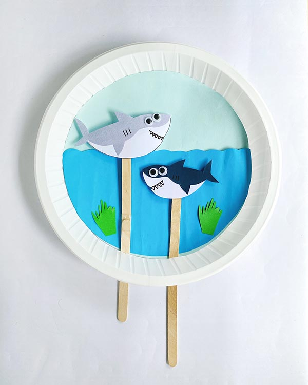 Overhead view of completed swimming sharks paper plate craft project. Gray shark is above wavy water line and navy shark is swimming below the surface.