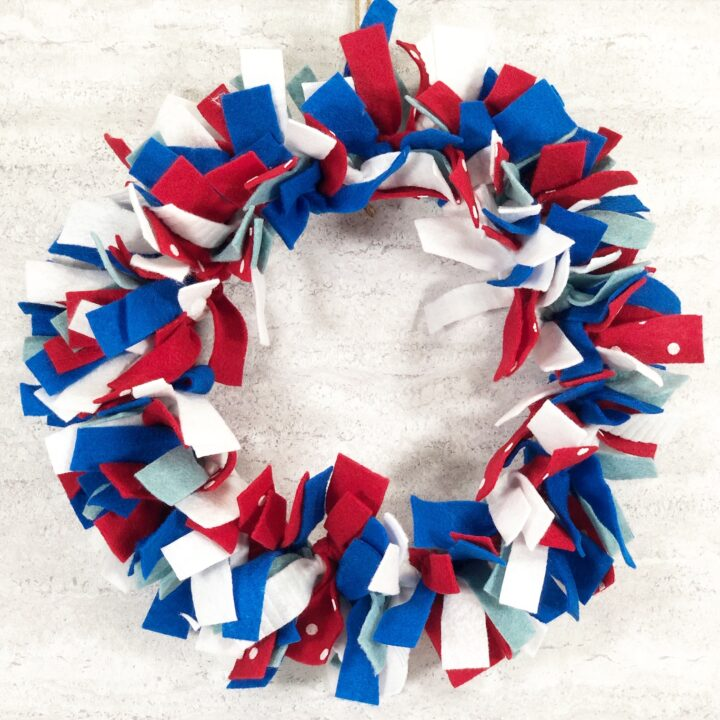Completed red white and blue felt wreath hanging on wall.