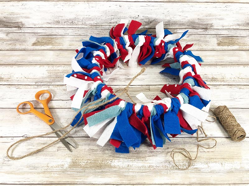 Finished red, white and blue felt wreath laying face down to add twine hanger to the back.