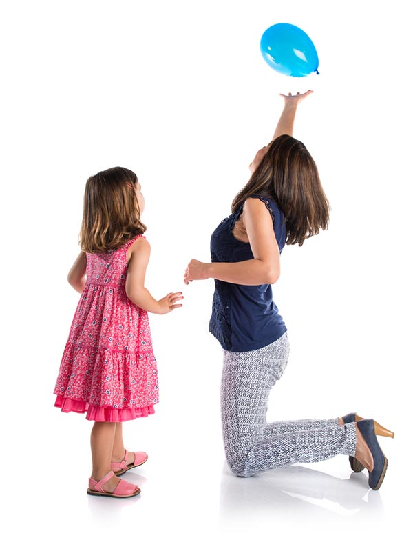 Young white girl with dark hair wearing a pink dress standing and watching as her mom (white woman with short dark hair wearing a navy tank top, light patterned pants, and high heels) kneels in front of her trying to keep a blue balloon in the air.