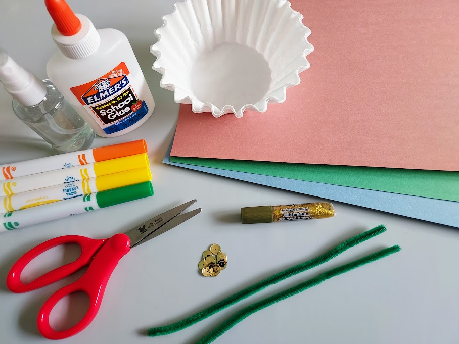 Various colors of construction paper, coffee filters, green chenille stems, sequins, glitter glue, scissors, orange, yellow, and green markers, and liquid glue on table.