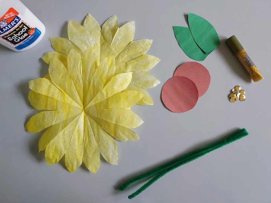 Yellow dyed coffee filters with petals cut, brown paper circles, green paper leaves, sequins, glitter glue, green pipe cleaners, and glue.
