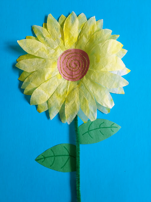 One finished coffee filter sunflower on blue paper with green stem and leaves. Center of flower is a brown construction paper circle with a glitter glue swirl.