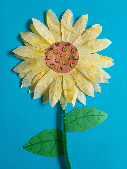 Completed sunflower made with coffee filters, construction paper, chenille stem and sequins glued to blue construction paper.