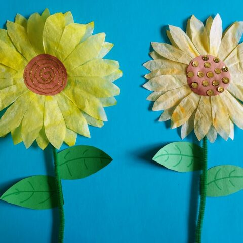 two completed coffee filter sunflower crafts on blue paper.
