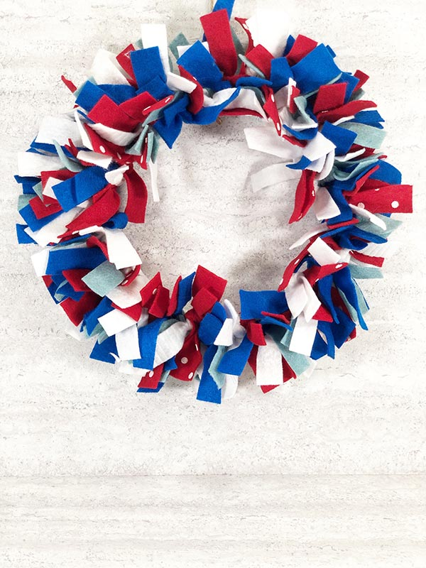 Completed red, white and blue no sew felt wreath hanging up for a festive Fourth of July decoration.