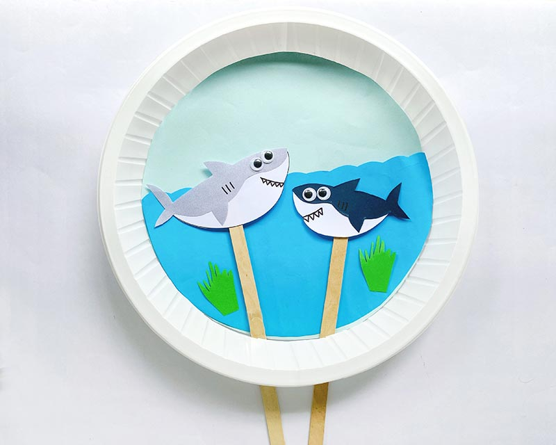 Overhead view of moving shark paper plate craft. Two paper shark puppets (one gray and white, the other navy and white) on popsicle sticks through a slit in a paper plate. Blue paper glued to back of plate to look like water.