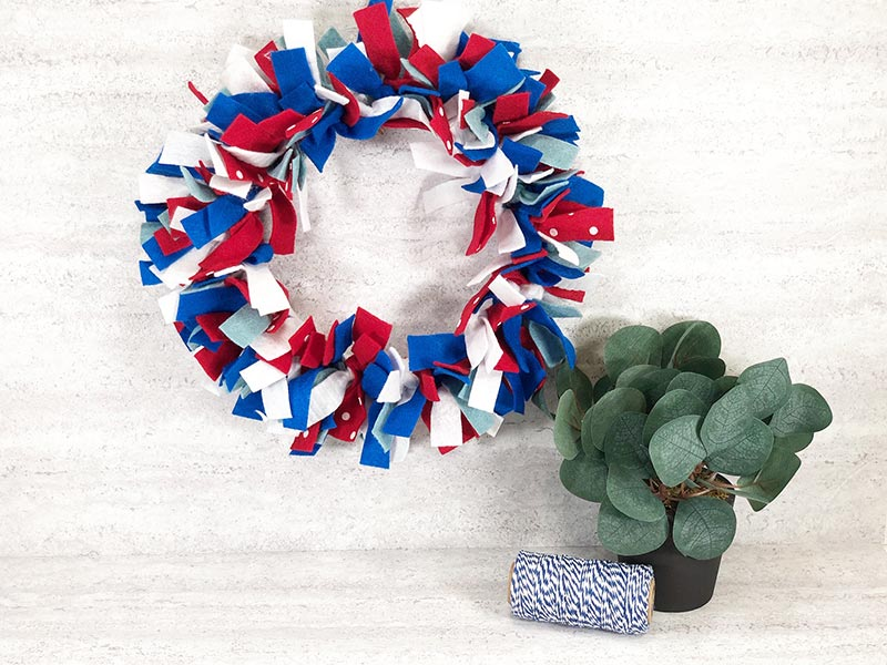 Fourth of July wreath made with red, white, and blue felt strips hanging on a white brick wall next to a small green decorative plant and a roll of twine.