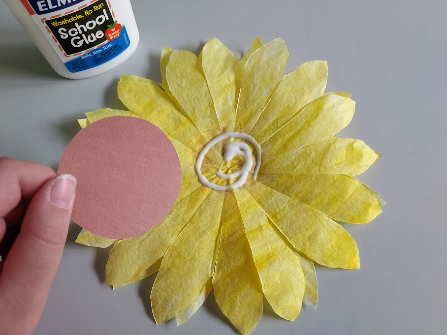 Gluing brown construction paper circle to center of coffee filter sunflower petals.
