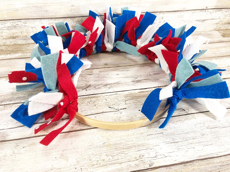 Wooden embroidery hoop almost full of tied on felt strips in red, white, and blue colors to make wreath for 4th of July.