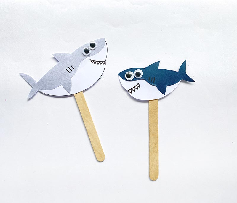 Two paper sharks (one gray with white and the other dark navy with white) attached to craft popsicle sticks to make shark puppets.