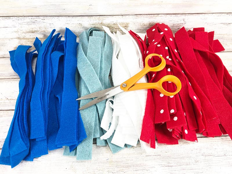 Piles of dark blue, light blue, white, red with white dots, and red felt strips with pair of scissors laying on top.