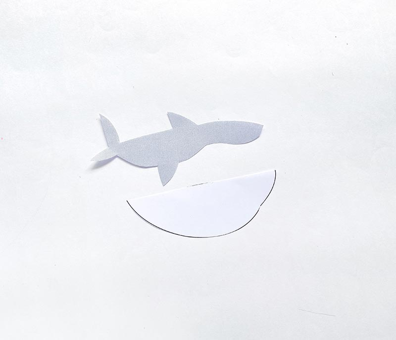 Top and bottom pieces for shark body cut out using gray and white paper.