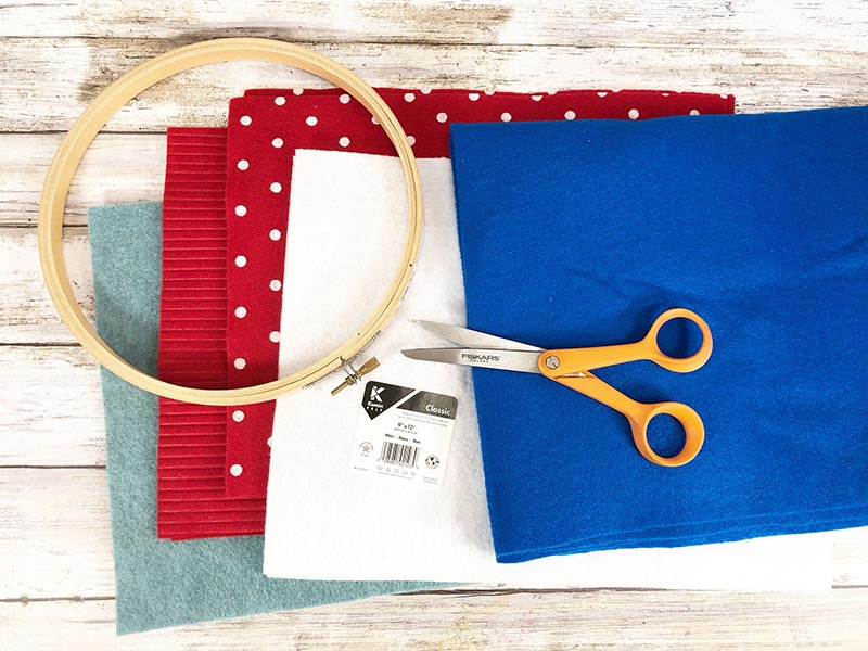 Overhead view of supplies for July felt wreath craft. Squares of light blue, red, red with white polka dots, white, and dark blue felt, wooden embroidery hoop, and scissors laying on top of the felt.