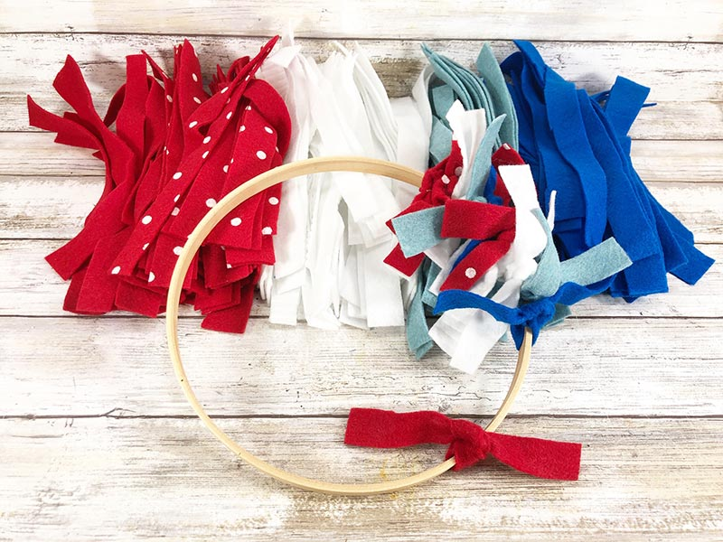 Overhead view of wooden hoop with a few felt strips tied onto it laying partially on top of piles of felt strips sorted by red, white, and blue colors.