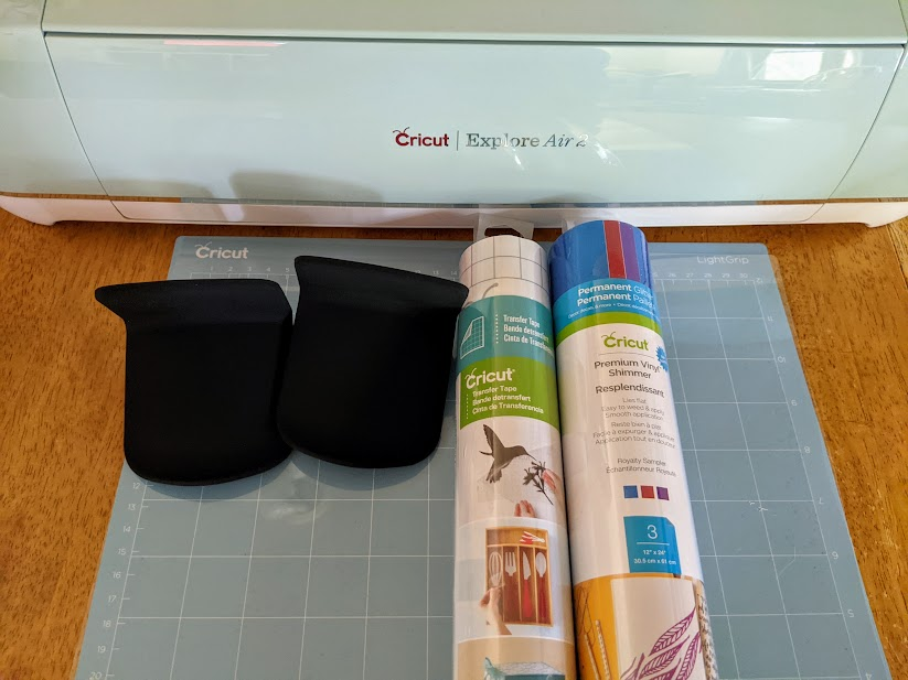 Cricut Explore Air 2 cutting machine, LightGrip machine mat, Premium Shimmer Vinyl, roll of Transfer Tape, and two black headphone hangers on the table for this project.
