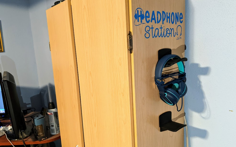 Finished DIY headphone station from angled side view to show blue vinyl Headphone Station design on the side of cabinet with headphones on hanging hooks below design in computer gaming room.