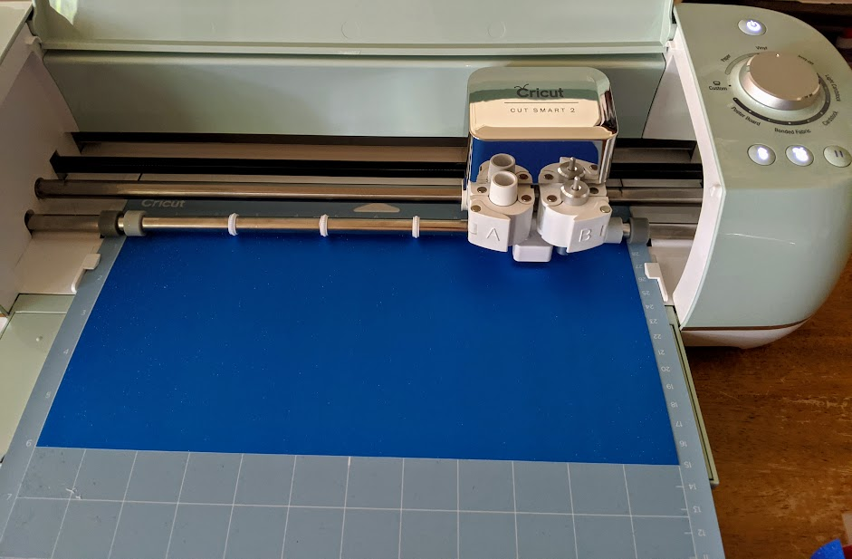 Machine mat with blue shimmer vinyl on it loaded and being cut by Cricut Explore Air 2 cutting machine.