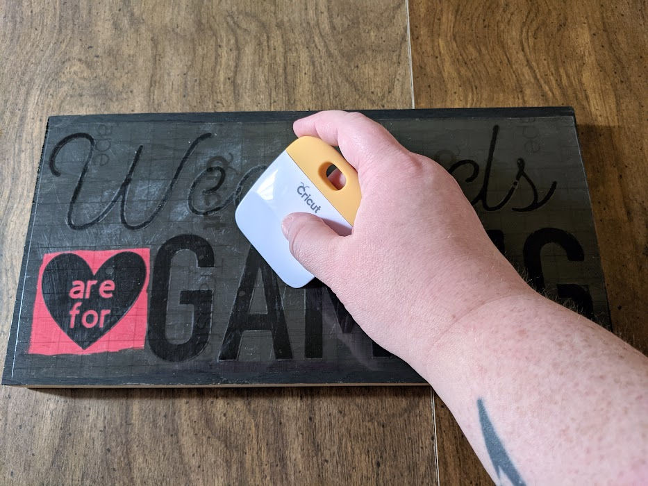 White woman's hand using scraper tool to apply vinyl to black and red painted wood sign.