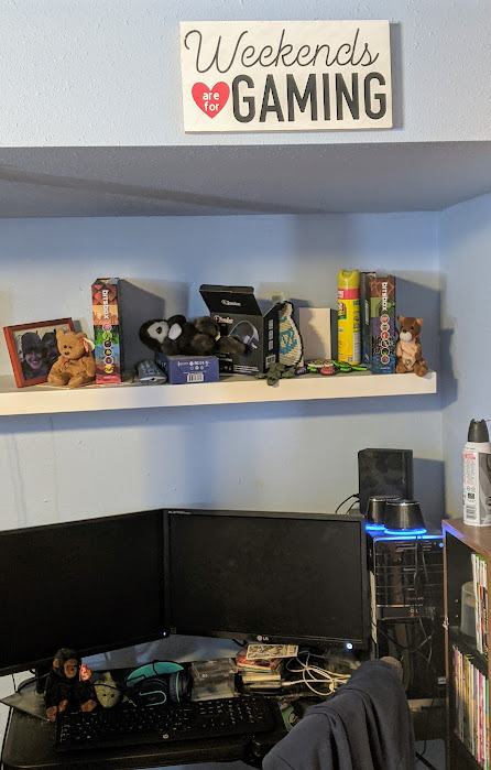Completed sign hanging on light blue wall above computer desk in computer gaming room.