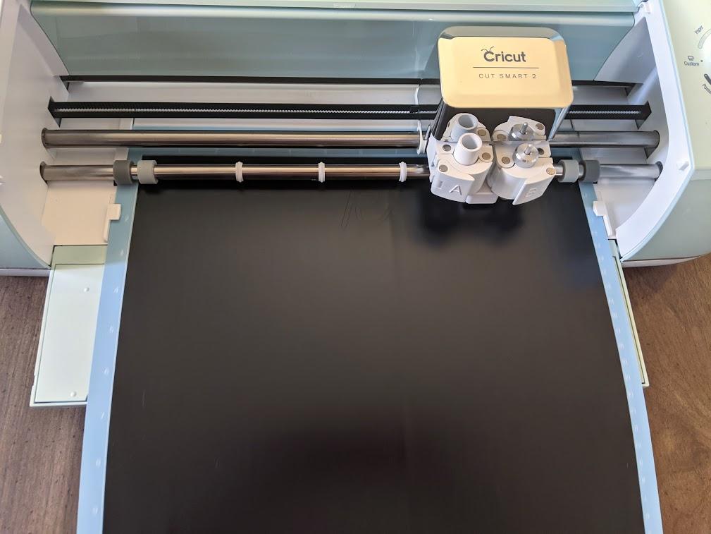 Machine mat with black vinyl loaded into Cricut cutting machine.