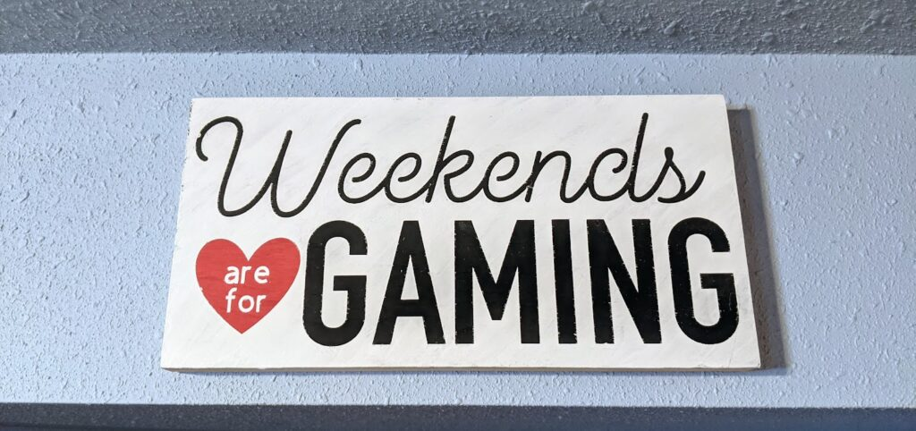 Handpainted sign that says Weekends are for Gaming hung on a light blue wall.