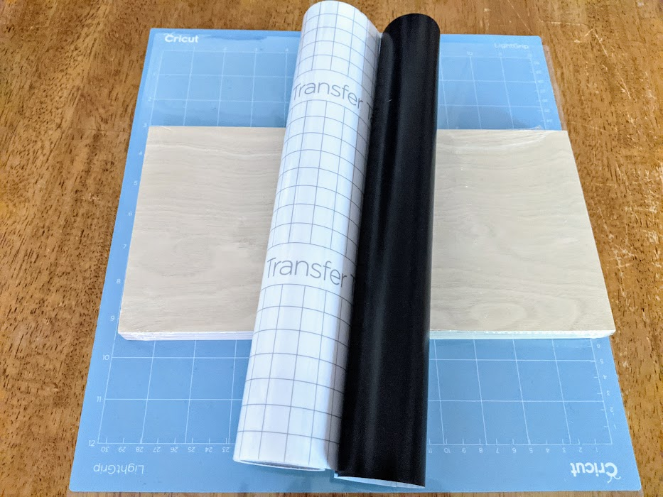 Blue Cricut machinemat, blank wooden canvas, roll of black vinyl, and roll of Transfer tape on table.