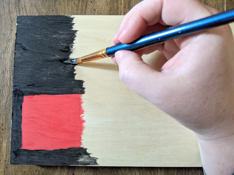 White woman's hand painting wooden sign black and red.