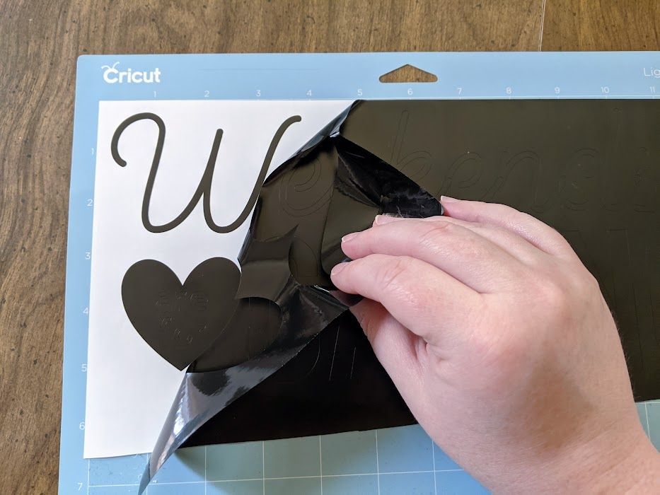White woman's hand peeling back excess black vinyl from design cut with Cricut machine.
