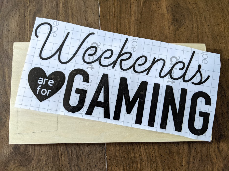 Black vinyl design with transfer tape over it. Design says Weekends are for (are for is inside a heart) Gaming. Design is laying at an angle over the top of a blank wooden sign.